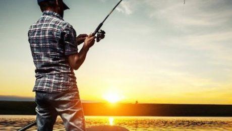 Um pescador fisgando um peixe, ao por do sol, em um dos rios do Mato Grosso